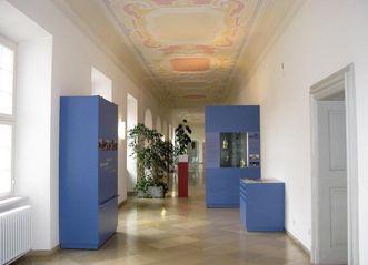Ausstellungsvitrinen in einem Flur der Gästeappartements; Foto: Staatliche Schlösser und Gärten Baden-Württemberg, Ortsverband Schussenried Wiblingen