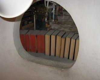 Eingebautes Loch zur Beleuchtung der Treppe hinter einem der Bücherregale